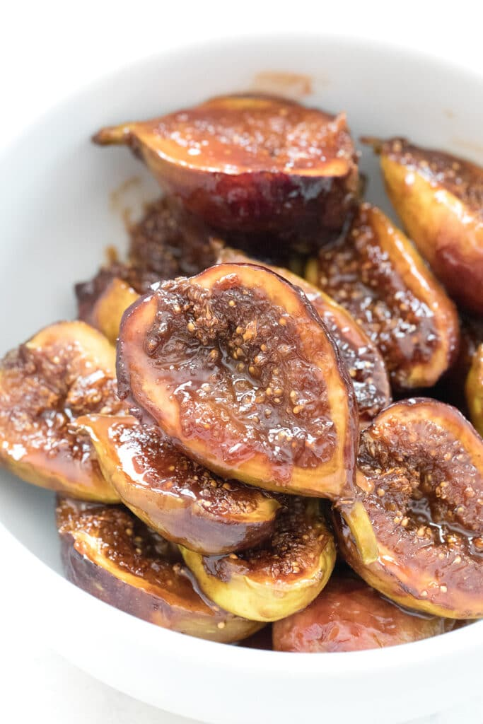 Overhead close-up view of caramelized figs in a white bowl