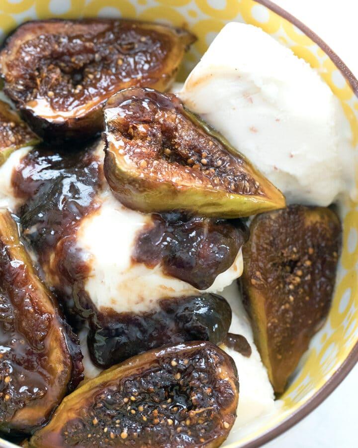 Overhead closeup view of caramelized figs over vanilla ice cream