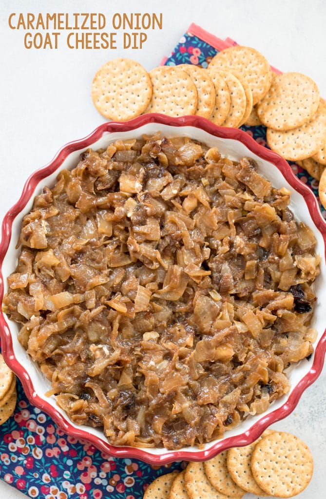 Overhead view of caramelized onion goat cheese dip in a pie plate, surrounded by crackers with recipe name at top