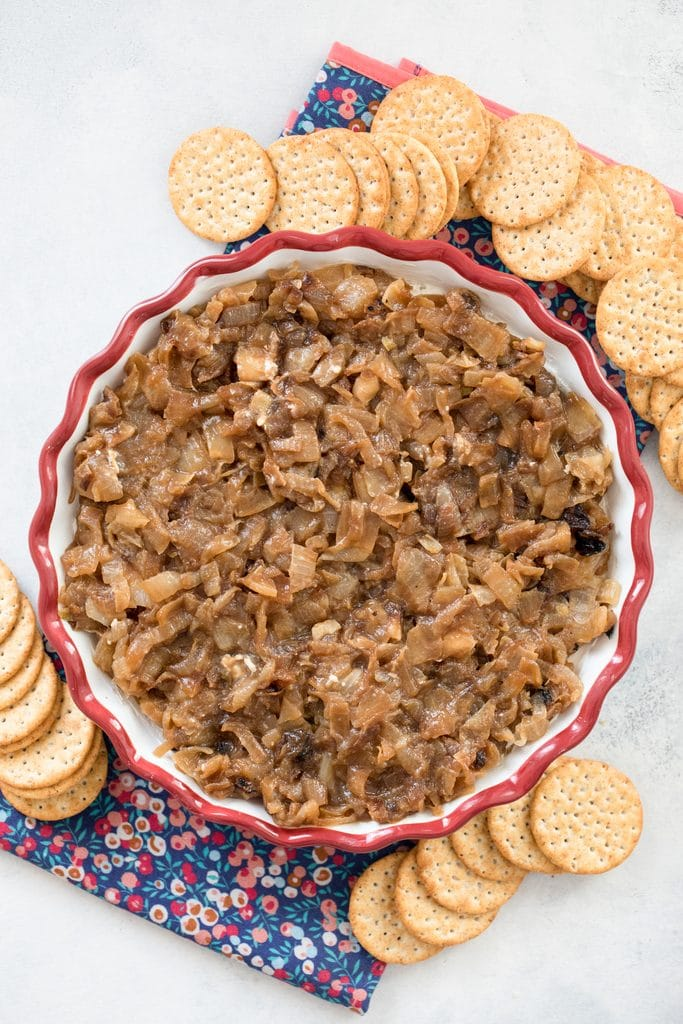 Overhead view from a distance of caramelized onion goat cheese dip in a pie plate, surrounded by crackers