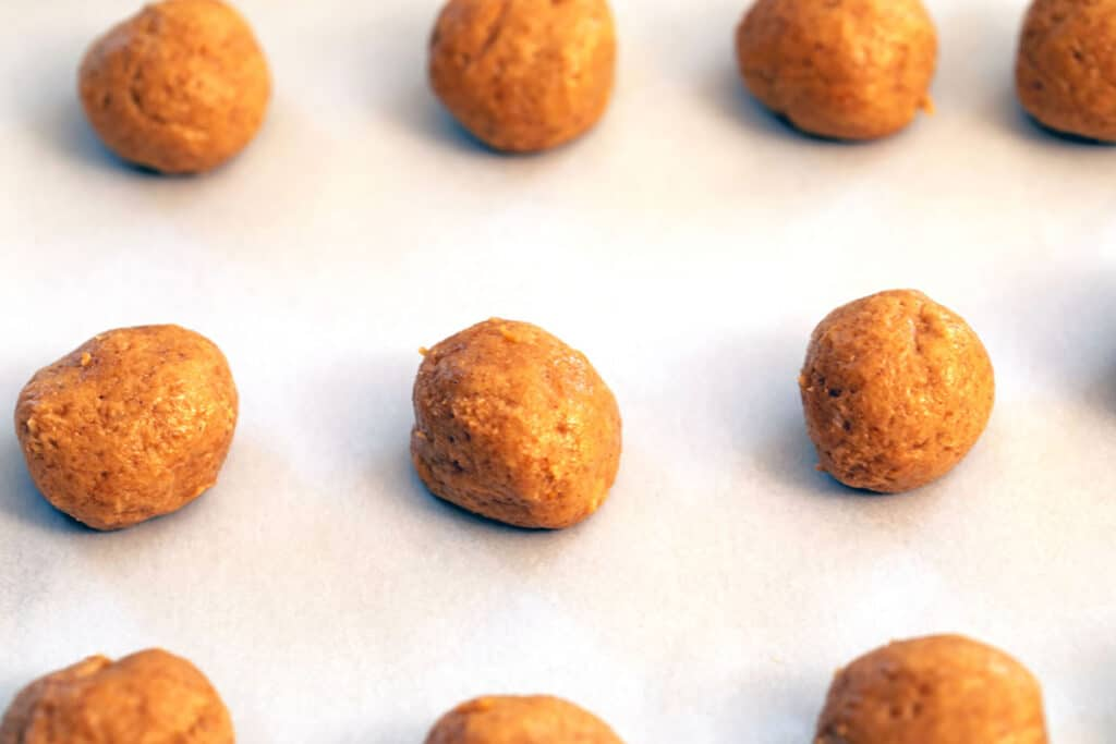 Carrot Cake truffle Oreo balls lined up on a parchment paper-line cookie sheet