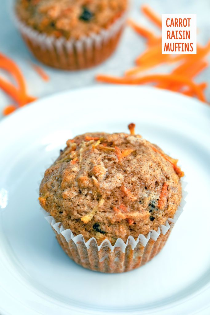 Overhead view of a Carrot Raisin Muffin on a white plate with shredded carrots and second muffin in the background and recipe title at top