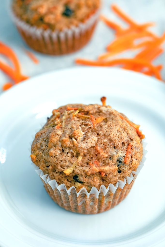 Overhead view of a Carrot Raisin Muffin on a white plate with shredded carrots and second muffin in the background