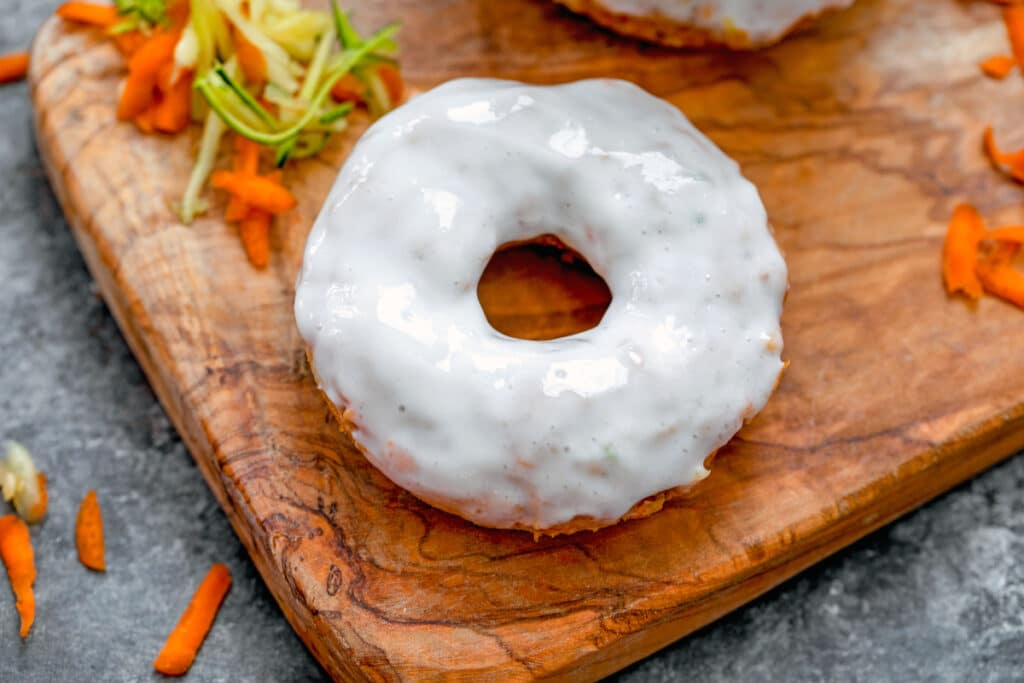 Landscape overhead view of carrot zucchini donut with Greek yogurt icing on wooden board surrounded by shredded carrots and zucchini