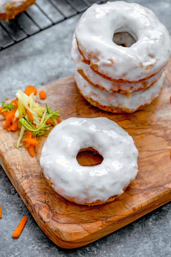 Overhead view of a carrot zucchini donut with Greek yogurt frosting on a wooden board with shredded carrot and zucchini and stack of donuts in background