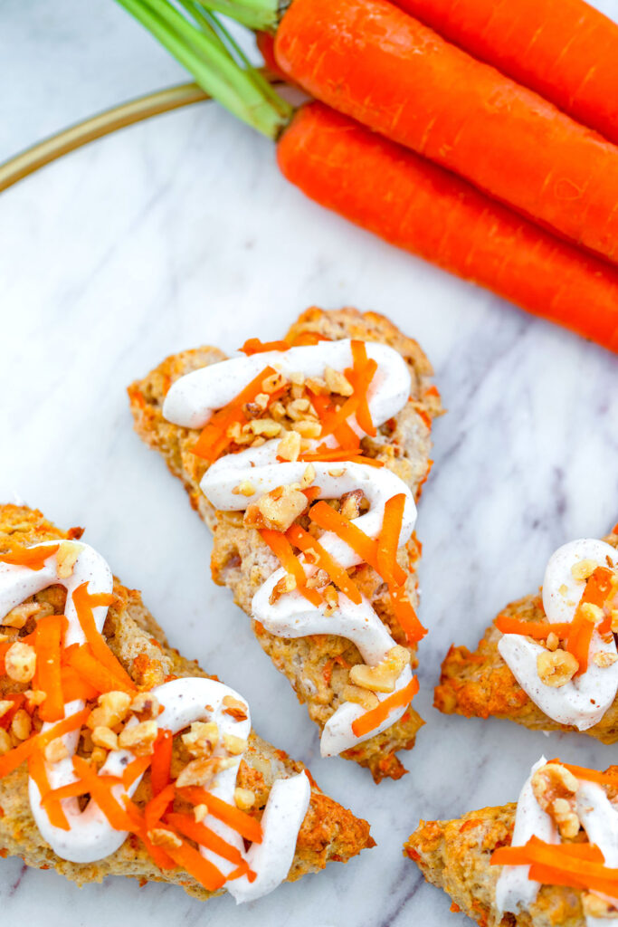 Overhead view of chai carrot cake scones drizzled with cream cheese frosting on a marble surface with bunch of carrots in the background