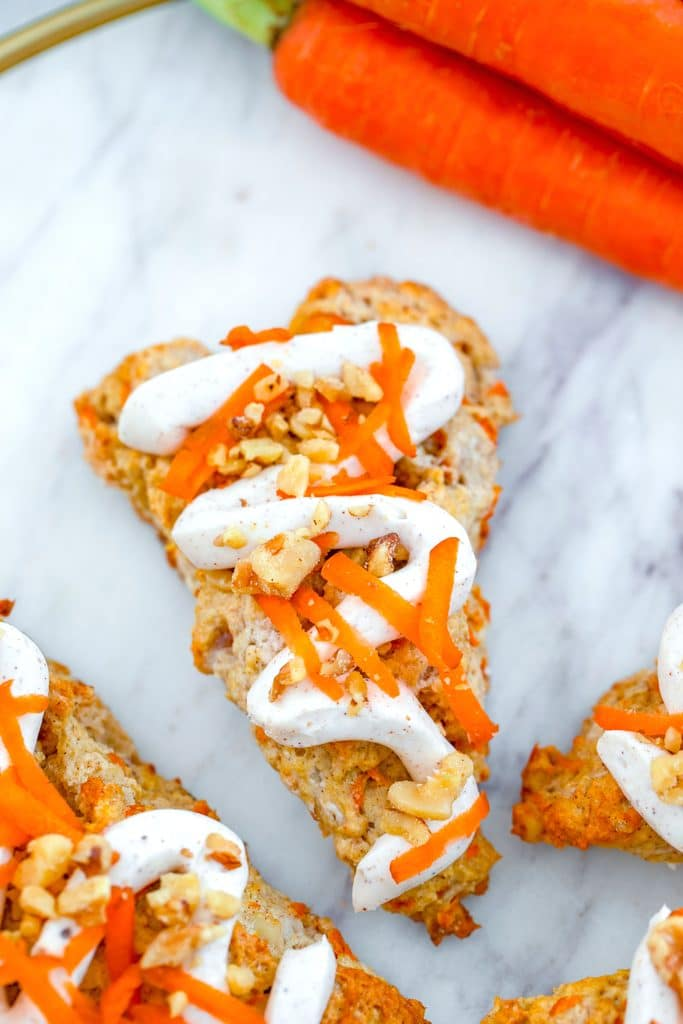 Overhead close-up view of a chai carrot cake scone drizzled with cream cheese frosting with bunch of carrots in the backgournd