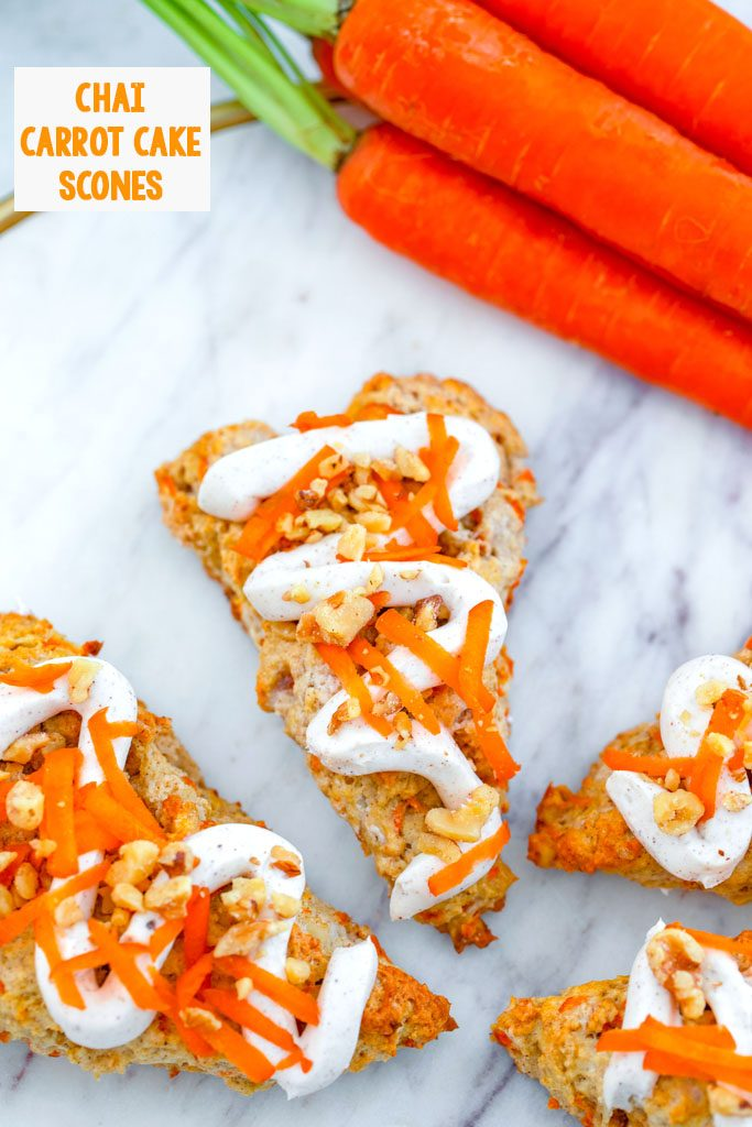 Overhead view of chai carrot cake scones drizzled with cream cheese frosting on a marble surface with bunch of carrots in the background and recipe title at top