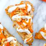 Overhead closeup view of a chai carrot cake scone with cream cheese icing and grated carrot