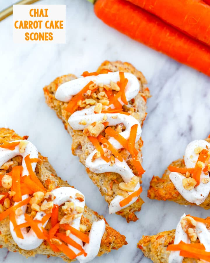 Overhead view of chai carrot cake scones on a marble platter with carrots in background and recipe title at top