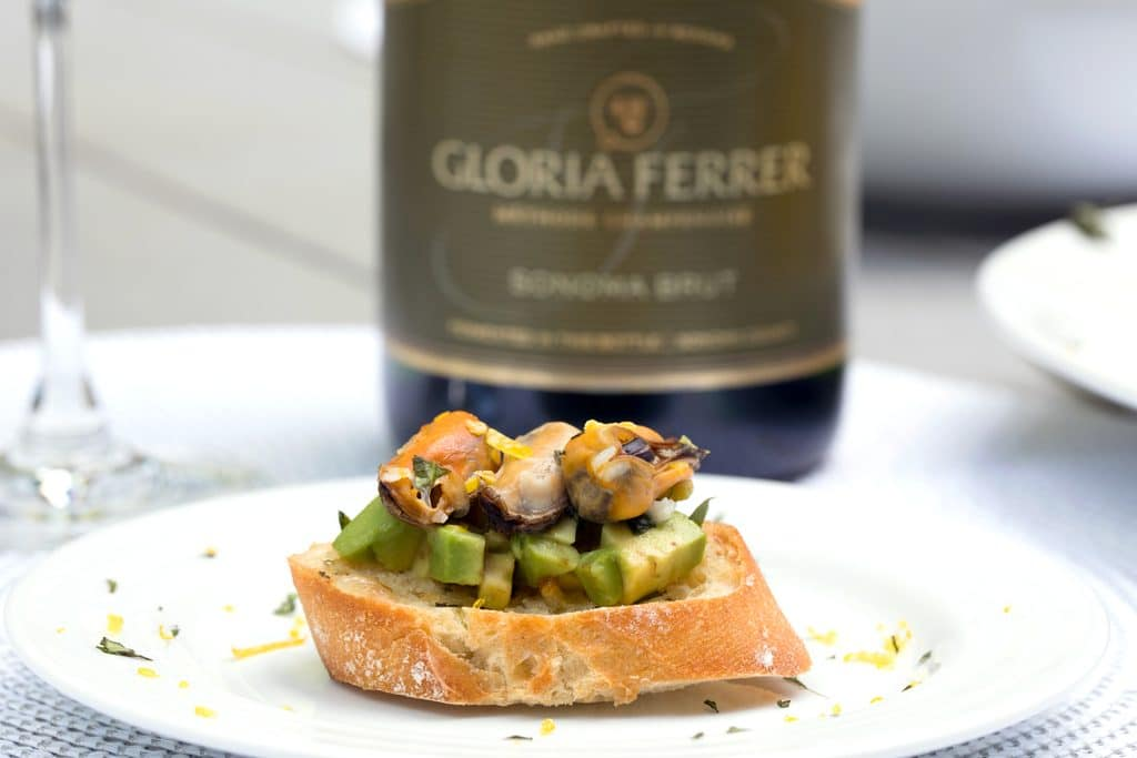 Sparkling Wine Mussel Crostini with Avocado, Grilled Lemon, and Basil -- The perfect party appetizer #GloriousBites   wearenotmartha.com