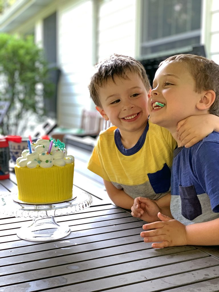 Charlie and Henry sitting outside with their birthday cake
