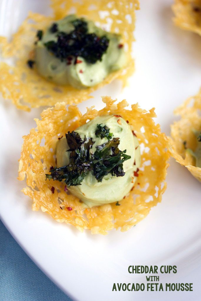 Overhead view of multiple cheddar cups filled with avocado mousse and topped with crispy kale on a white platter with recipe title at the bottom of the image
