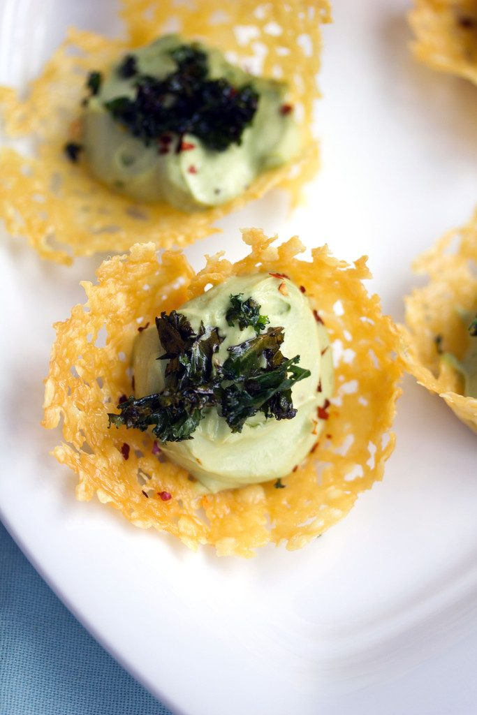 Overhead view of multiple cheddar cups filled with avocado mousse and topped with crispy kale on a white platter