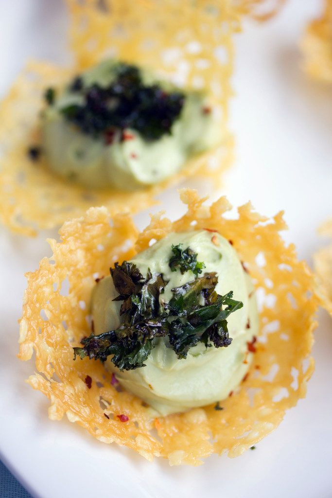 Overhead closeup view of a cheddar cup filled with avocado feta mousse and topped with crispy kale