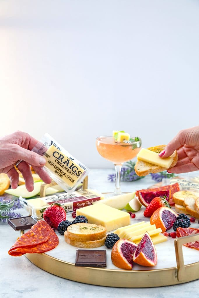 Head-on view of a cheese board with fruit, chocolate, meat, and crackers with two hands reaching out to grab cheese and a pear old Cuban cocktail in the background