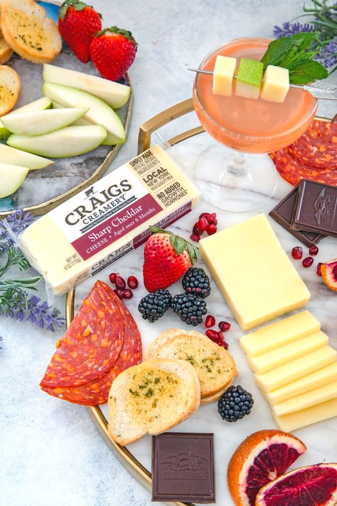 Overhead view of block of Craigs Creamery cheddar on a marble board with lots of meat, fruit, crackers, and chocolate, with pear old Cuban cocktails