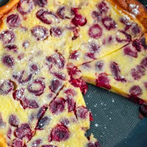 "Overhead view of cherry clafoutis in skillet with slice taken out and ""Cherry Clafoutis"" text at top"