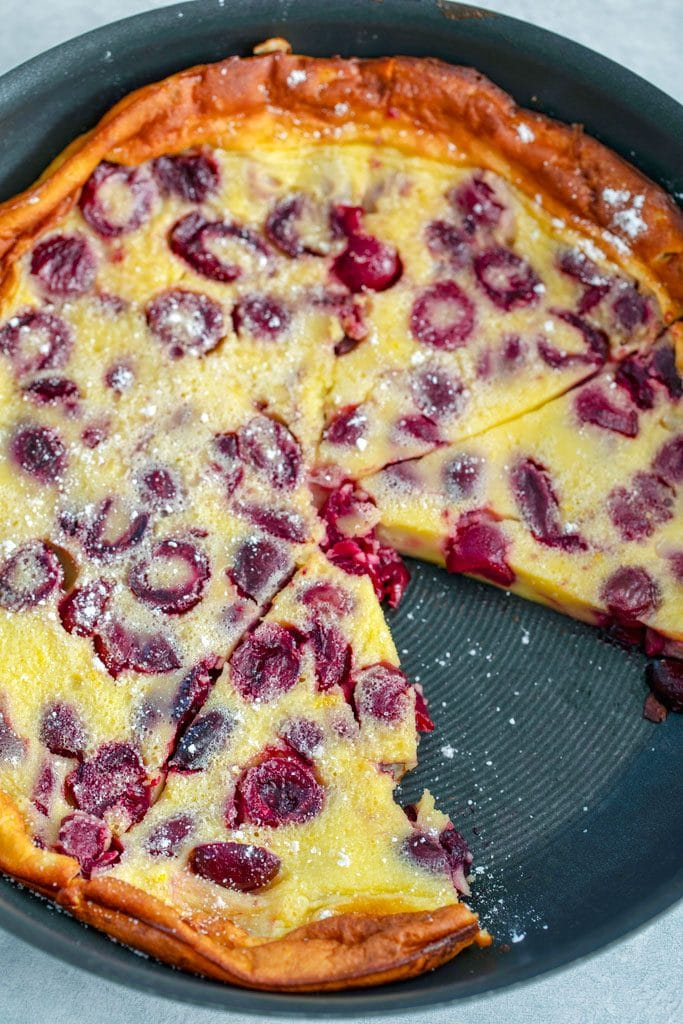 Overhead view of cherry clafoutis in skillet with slice taken out