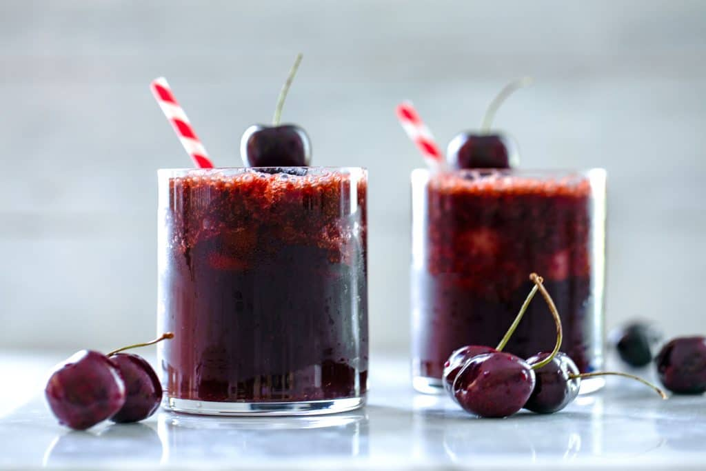Landscape view of two glasses of cherry rum and coke with red and white striped straws, cherry garnishes, and cherries scattered on table