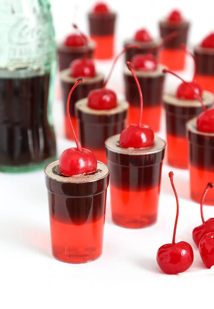 Cherry cola jello shots in little cups with maraschino cherry garnish