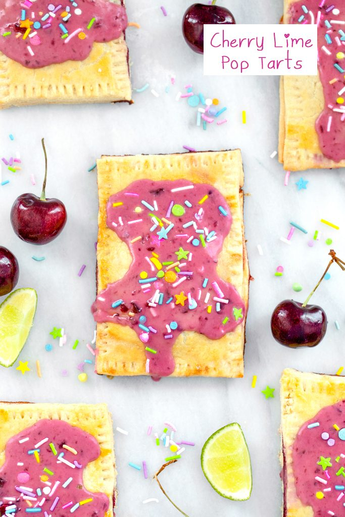 Overhead view of a cherry lime pop tart on a marble surface with more pop tarts, cherries, limes, and sprinkles all around and recipe title at top
