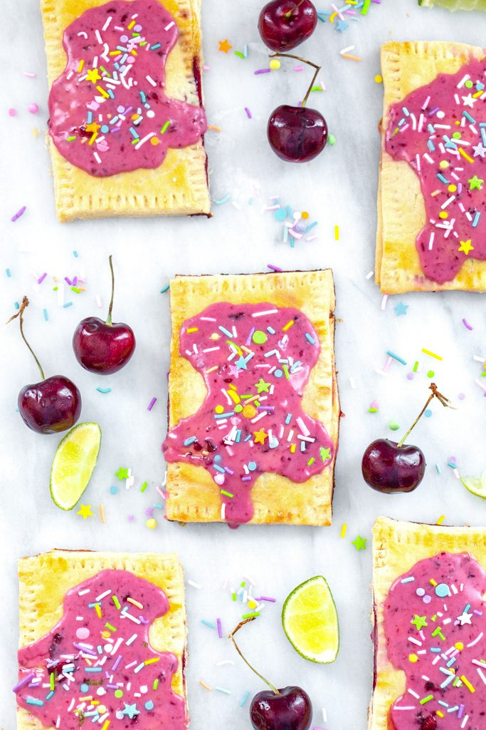 Bird's eye view of multiple cherry lime pop tarts on a marble surface with cherries, limes, and sprinkles all around