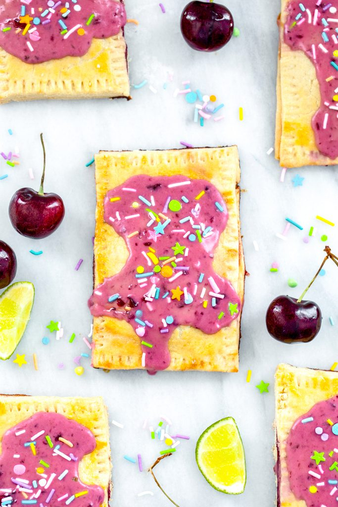 Overhead view of a cherry lime pop tart on a marble surface with more pop tarts, cherries, limes, and sprinkles all around