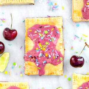 Overhead close-up view of a cherry lime pop tart on a marble surface with more pop tarts, cherries, limes, and sprinkles all around