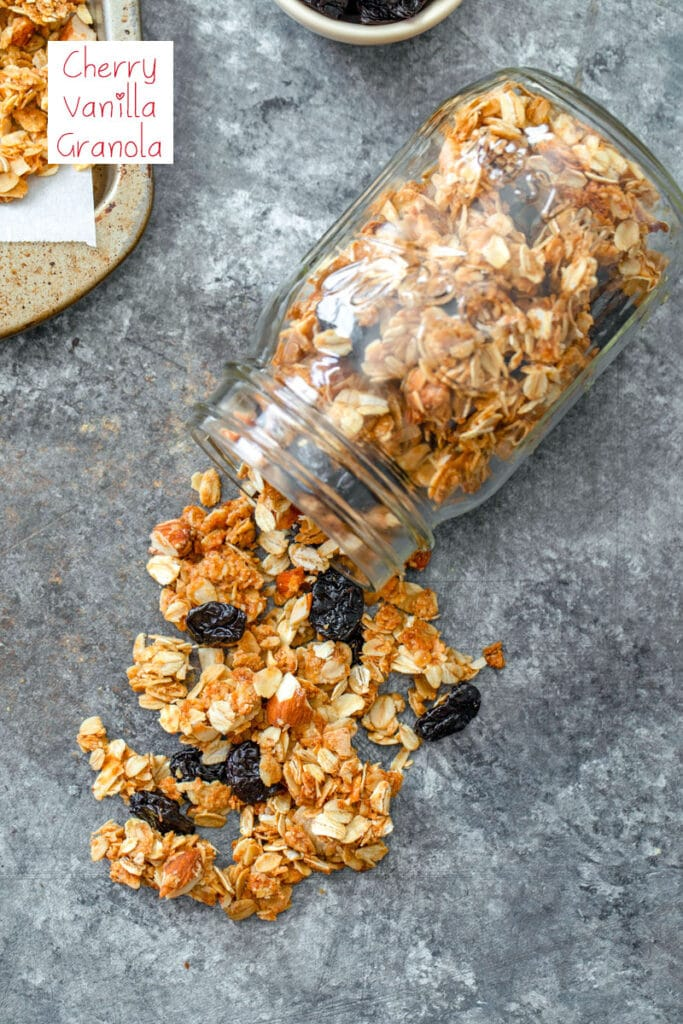 Overhead view of a mason jar with cherry vanilla granola spilling out of it with recipe title at top