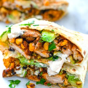 These Chicken, Avocado, and Corn Burritos are topped with feta sauce and make for a fresh and flavorful weeknight dinner that's incredibly quick and easy!