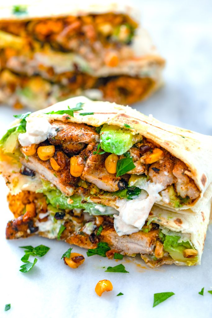 Chicken, avocado, and corn burritos cut in half and stacked on each other to showcase ingredients with feta sauce drizzled on them
