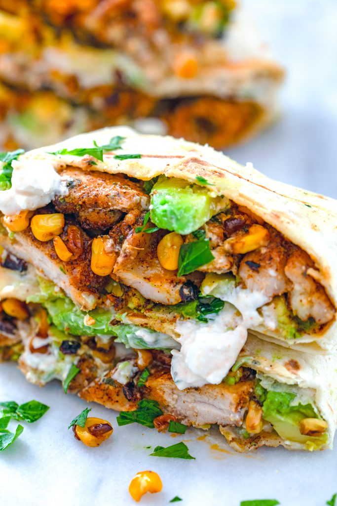 Close-up head-on view of a chicken, avocado, and corn burrito with feta sauce cut in half to show all of the ingredients