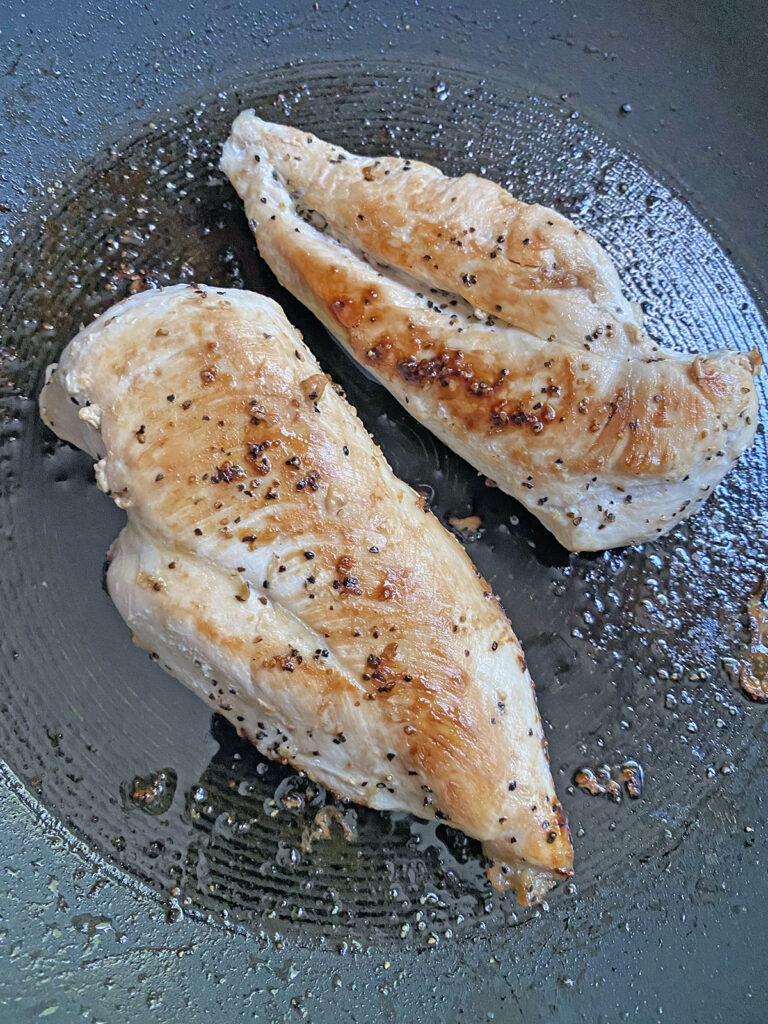 Chicken Breasts cooking in a skillet in olive oil