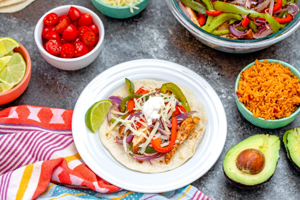 Landscape view of a chicken fajita on a plate surrounded by bowls of toppings (tomatoes, cheese, lime wedges, Spanish rice), half an avocado, and more chicken and veggies