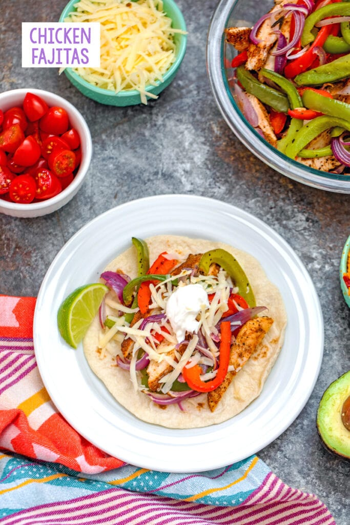 Overhead view of a prepared chicken fajita on a plate surrounded by a bowl of sliced chicken and vegetables and bowls of toppings with recipe title at top