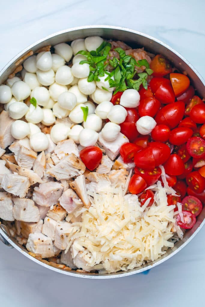 Overhead view of risotto in saucepan topped with chicken, mozzarella balls, cherry tomatoes, grated parmesan cheese, and chopped basil