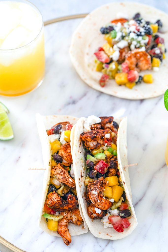 Overhead view from a distance of a marble tray with two chili lime shrimp tacos with fruit salsa with an open-faced taco in the background and an orange margarita and lime wedge on the side