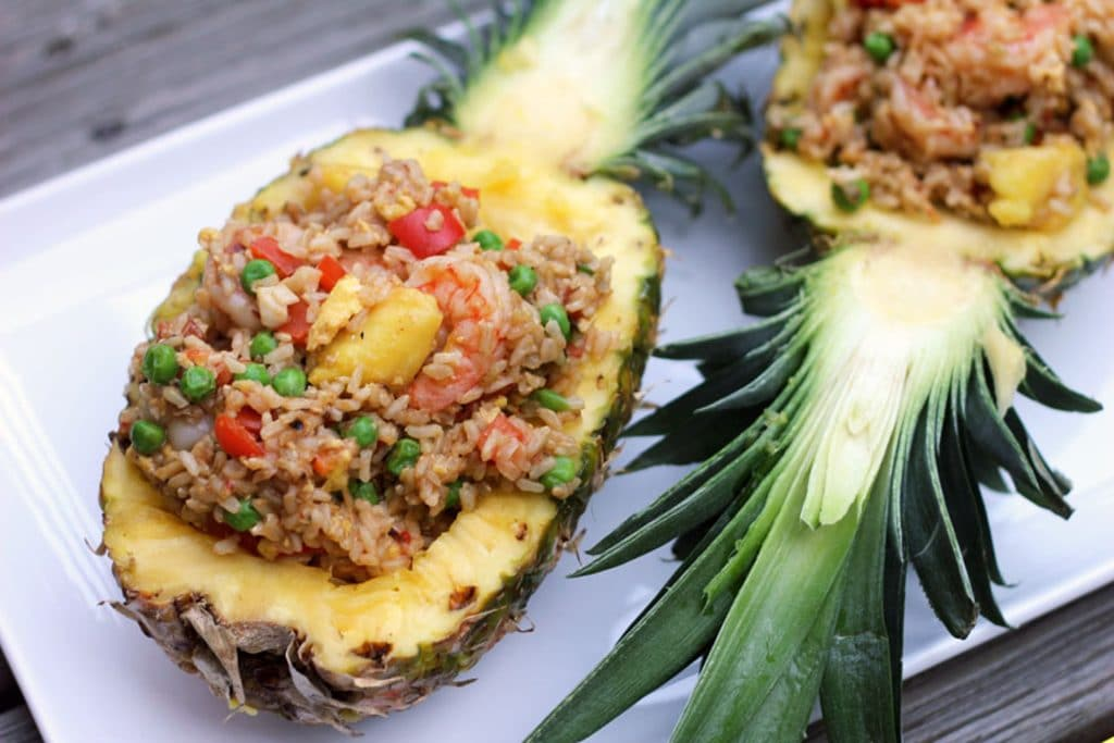 Two pineapple halves filled with chili mango shrimp pineapple fried rice served on a white platter