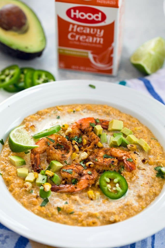 Head-on vide of chilled Mexican corn bisque topped with spicy shrimp, jalapeño slices, grilled corn kernels, diced avocado, and lime wedges with half an avocado, jalapeño slices and container of heavy cream in the background