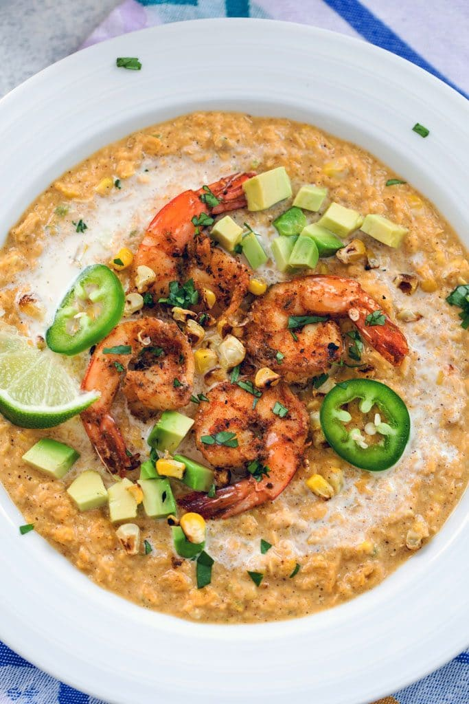 Bird's eye view closeup of Mexican corn bisque topped with spicy shrimp, sliced jalapeños, grilled corn kernels, lime wedges, and chopped cilantro in a white bowl