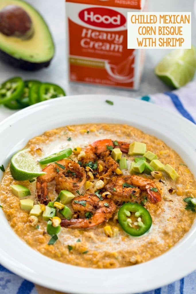 "Head-on vide of chilled Mexican corn bisque topped with spicy shrimp, jalapeño slices, grilled corn kernels, diced avocado, and lime wedges with half an avocado, jalapeño slices and container of heavy cream in the background and ""Chilled Mexican Corn Bisque with Shrimp"" in text at the top"