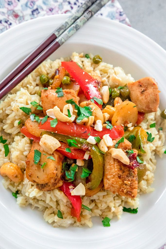 Overhead closeup view of chipotle chicken with cashews, red and green peppers, and peas over rice in a white bowl with chopsticks