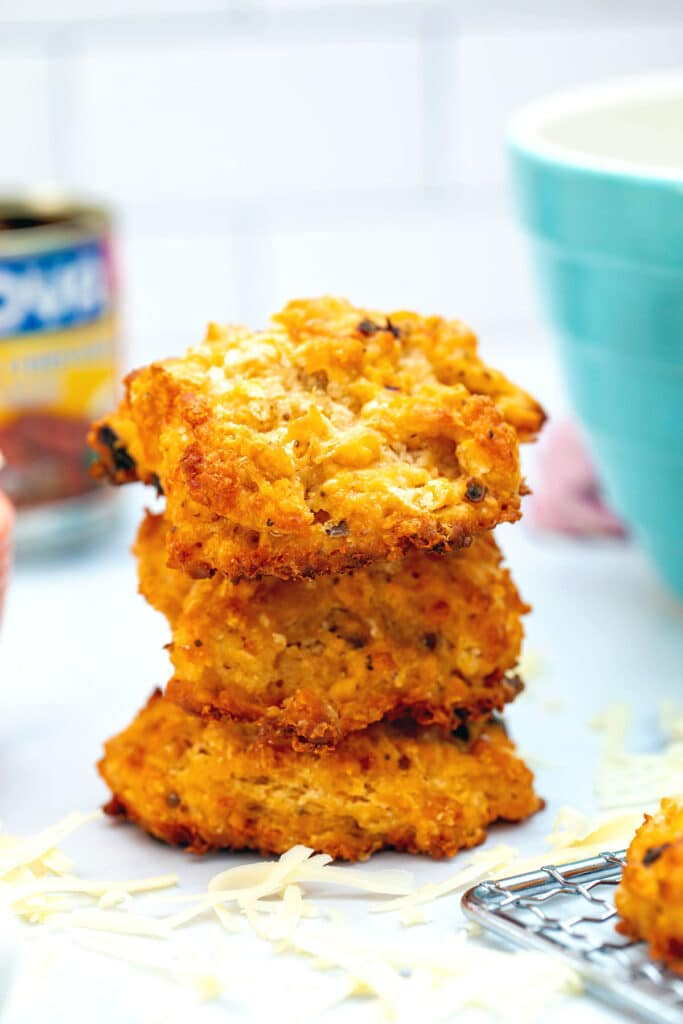 Head-on view of a stack of three chipotle cheddar biscuits with can of chipotle peppers and mixing bowl in backgorund