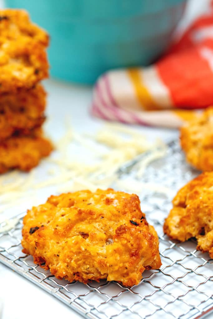 Head-on closeup view of a chipotle cheddar biscuit with shredded cheese and more biscuits in background