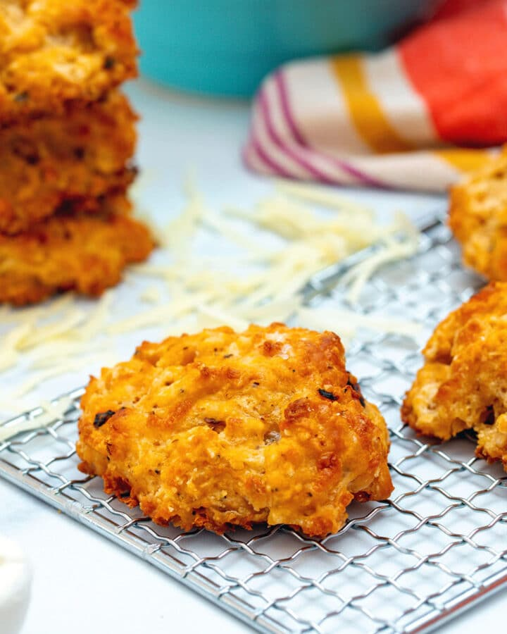Head-on view of a chipotle cheddar biscuit on a baking rack with more biscuits and shredded cheese in background