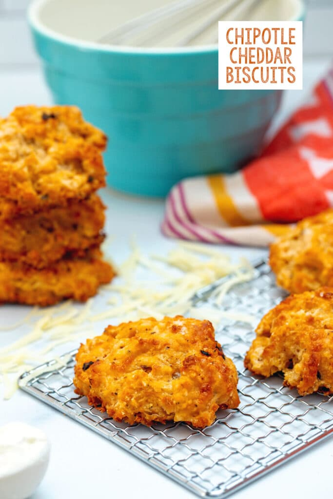 Head-on view of a chipotle cheddar biscuit on a baking rack with shredded cheese, more biscuits, and a mixing bowl in the background with recipe title at top