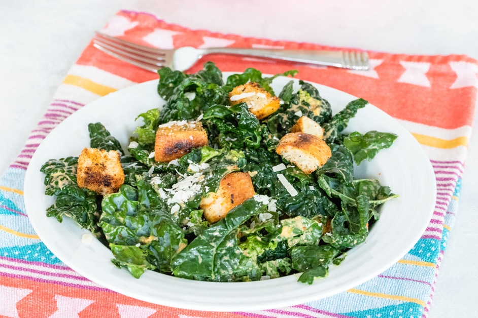 Horizontal photo of chipotle kale Caesar salad on red, yellow, and blue towel, with fork in the background