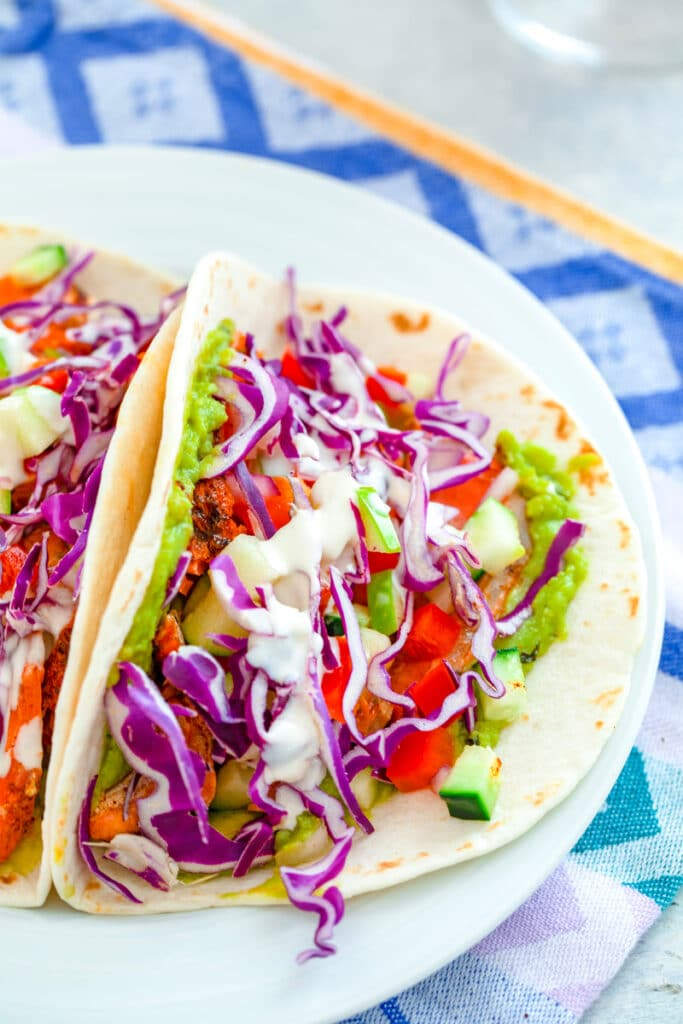 Overhead view of a white plate with two fully loaded chipotle-rubbed grilled salmon tacos with red cabbage, apple cucumber salsa, guacamole, and mayo drizzle