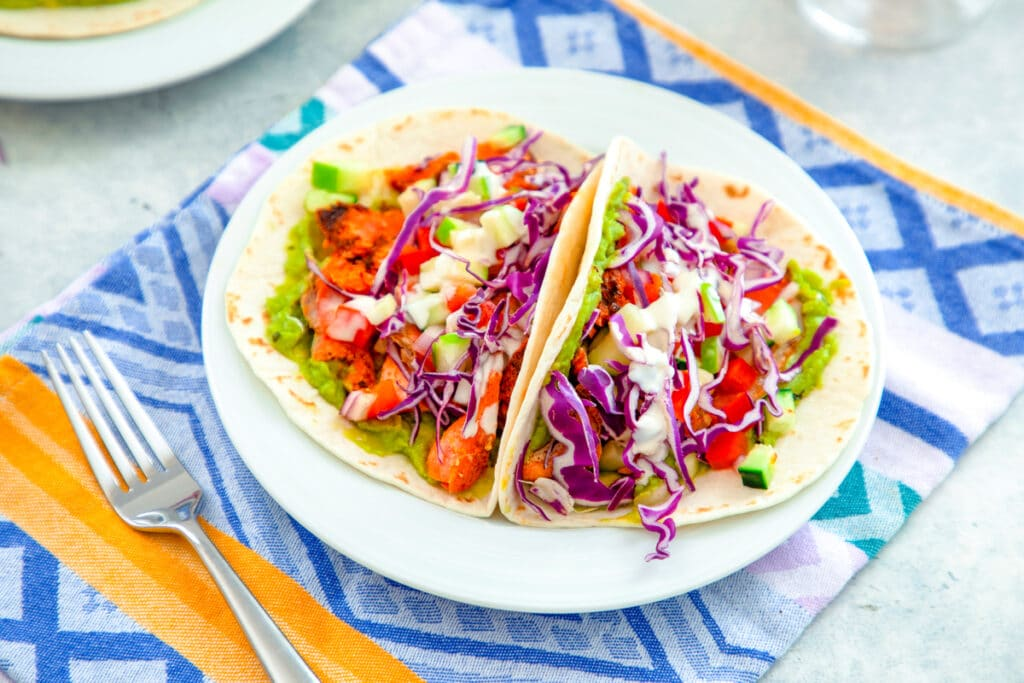 Overhead landscape view of two tacos on a white plate with chipotle-rubbed grilled salmon, red cabbage, apple cucumber salsa, mashed avocado, and mayo drizzle on a colorful towel with fork